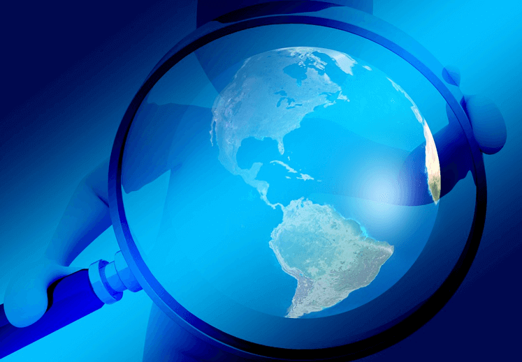 Image of a figure holding a magnifying over the globe