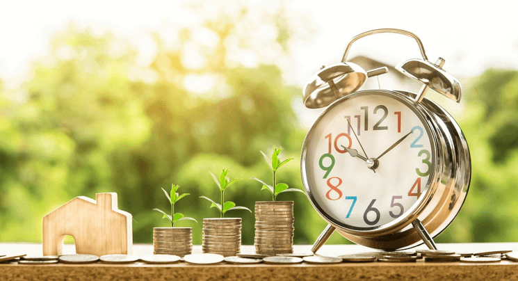 Image of three plants growing from stacks of coins beside an alarm clock