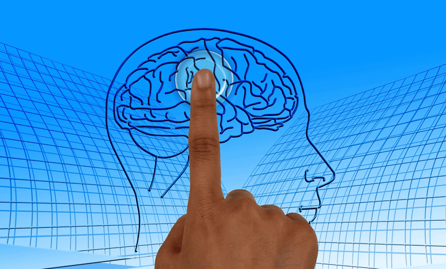 Image of a hand touching a picture of a brain, activating light