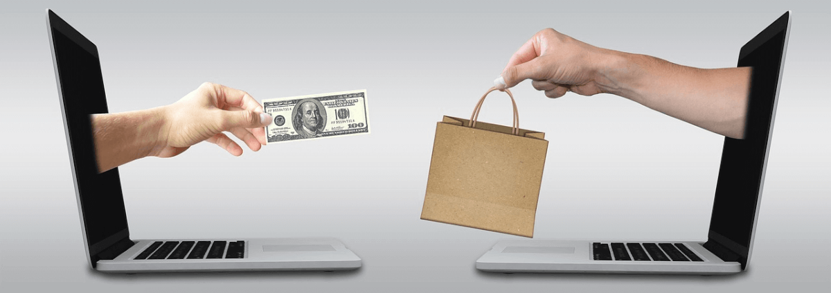 Image of a hand leaving a monitor holding cash, and an opposing monitor delivering goods, representing Ecommerce