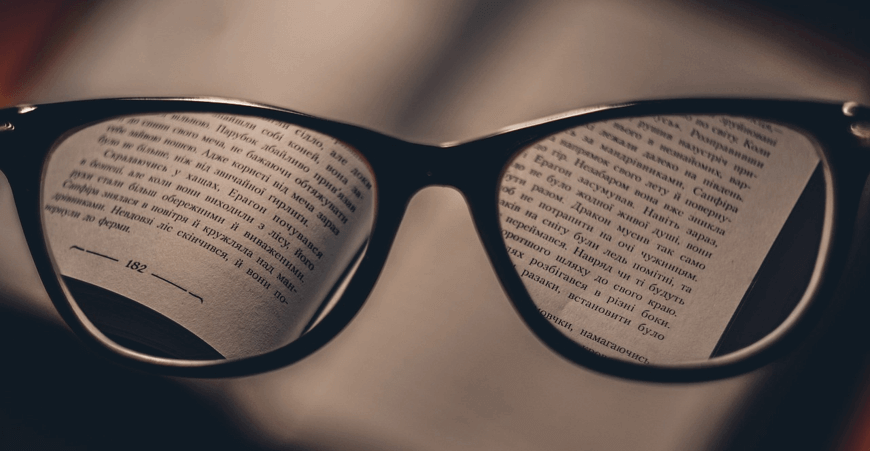 Image of a book through the lenses of reading glasses