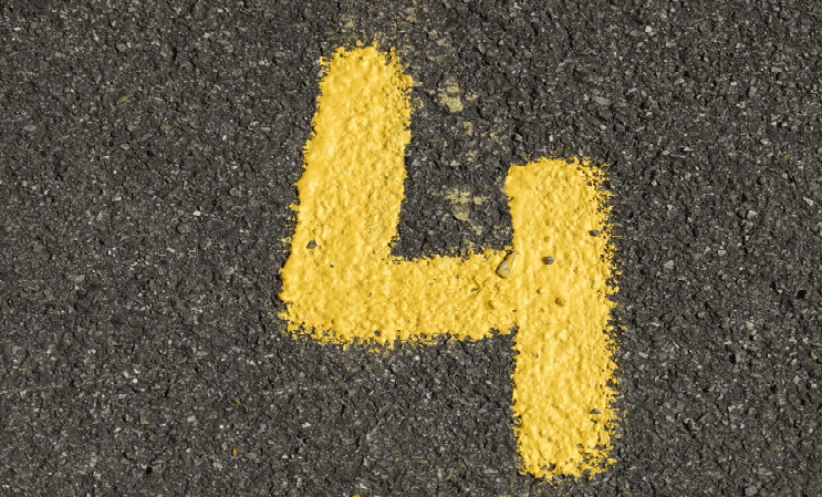"Image of the number ""4"" chalked in yellow onto asphalt"