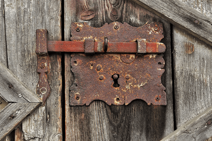 Image of a gateway with a rusted padlock.