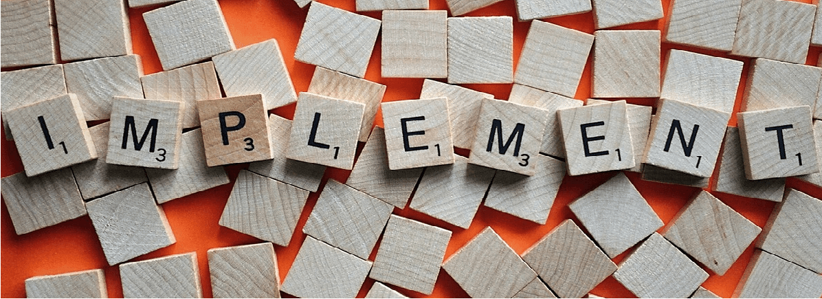"Image of scrabble game pieces spelling the word ""Implement"""