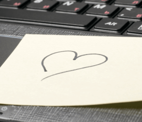 Image of a heart drawn on a sticky note attached to a laptop keyboard.
