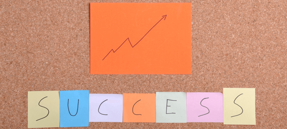 Image of post-it notes spelling out success and a simple line graph indicating growth.