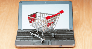 An image of a miniature shopping cart standing on a laptop computer