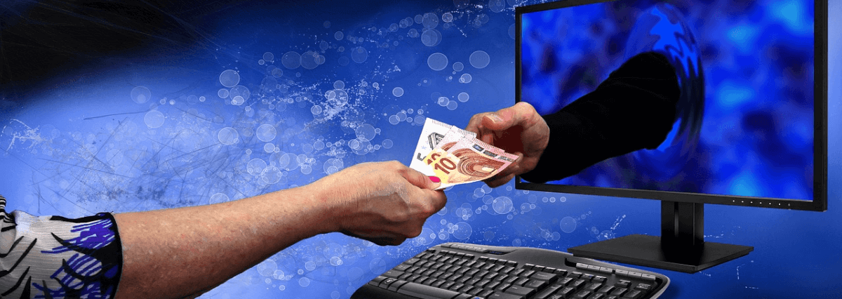 Abstract image of two hands exchanging currency through a computer monitor