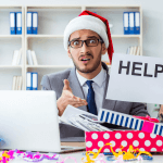 "Image of a businessman with a Santa hat in front of a laptop holding a sign that reads ""Help!"""
