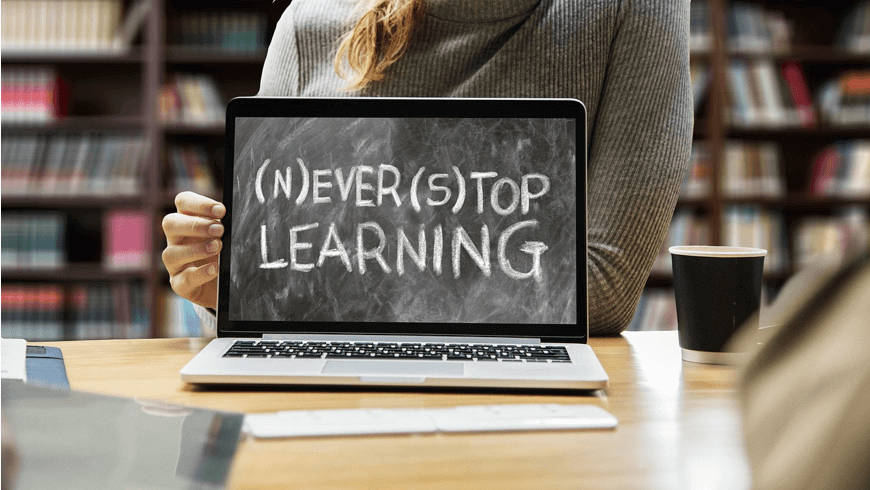 "Image of a female student sitting in front of a laptop that says ""never stop learning"", used to represent machine learning in NLP"