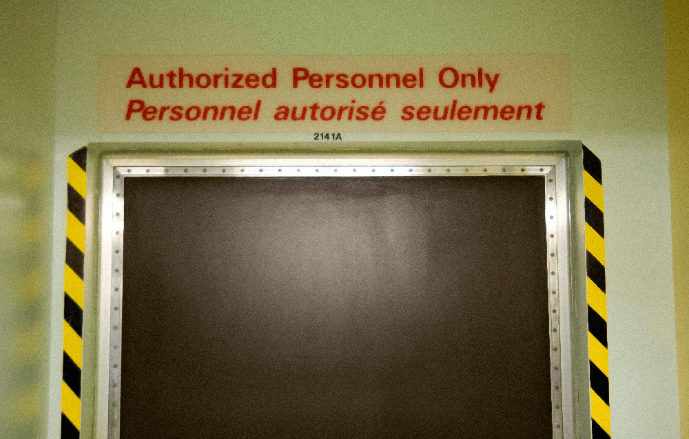 """A closed door with a red warning above it that reads """"Authorized Personnel Only&quot"""