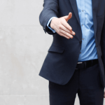 Image of a sales representative outstretching his hand in greeting.
