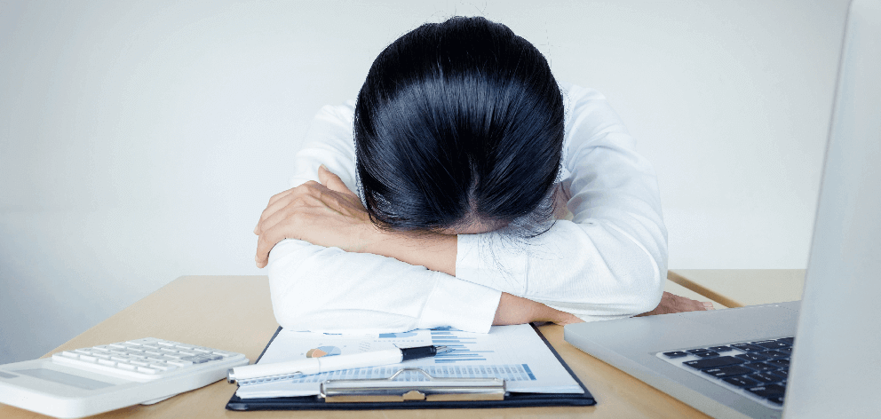 An exhausted woman in business attire resting her head in her arms at her desk