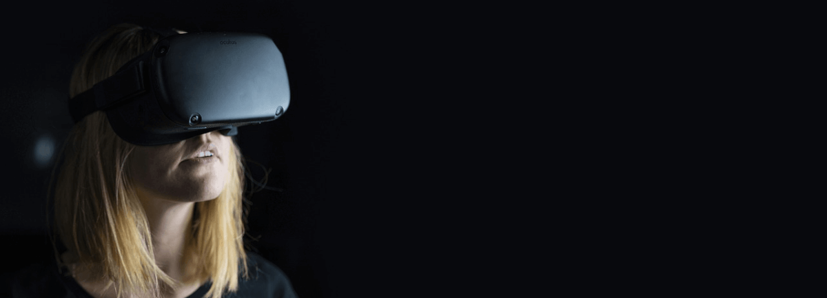 Image of a woman wearing a VR headset in the dark, representing the Ecommerce trend toward virtual and augmented reality